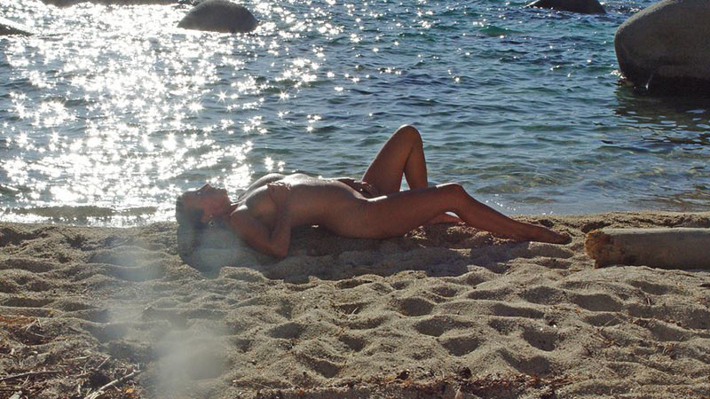 Aged MILF tanning her hot body on the nudist beach