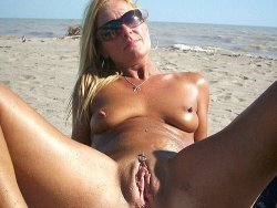 older wife spreading wide on the nudist beach for everyone to see