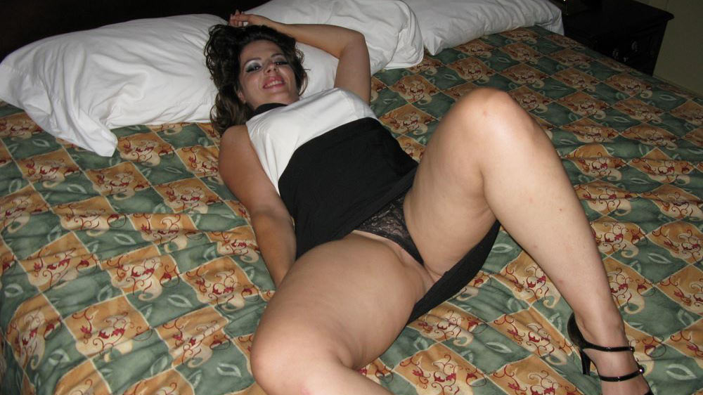 Chubby MILF in a sexy tight dress spreads on the bed