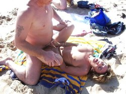 Mature swinger in a threesome on the nudist beach
