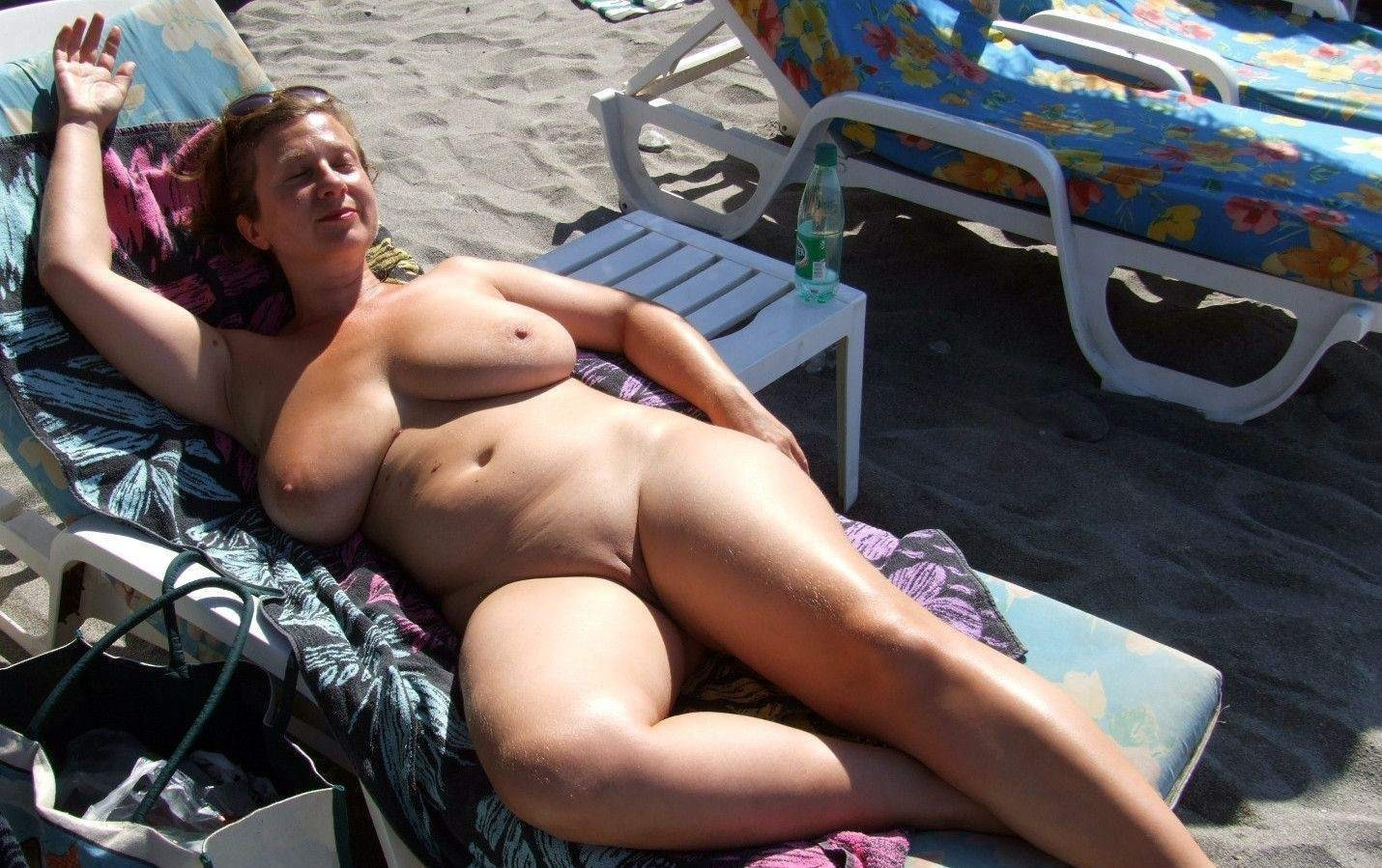 Curvy busty wife sun-bathing nude on the beach
