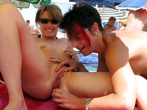 Shameless MILF fucks her girlfriend with a dildo while everyone on the nudist beach watches.