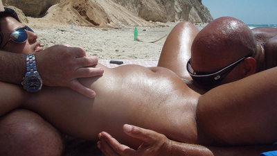 Chubby older wife in the middle of a threesome on the nudist beach