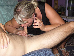 MILF gives a blowjob while on the phone